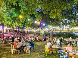 Photo de l'exterieur de la Guigette, avec des tables de couleurs festives,